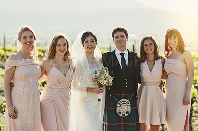 Buy stock photo Portrait of a cheerful bride and groom standing together with the bride's maids arm in arm outside