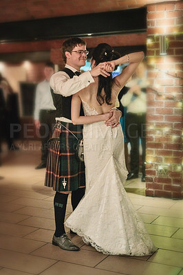 Buy stock photo Shot of a cheerful bride and groom having the first dance of the evening together on the dance floor inside of a building