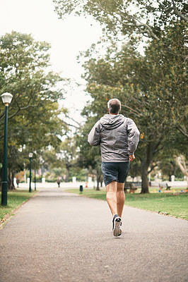 Buy stock photo Rearview shot of a senior man out for a run in the park