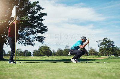 Buy stock photo Shot of a focused young male golfer looking at a golf ball while being seated on the grass outside during the day