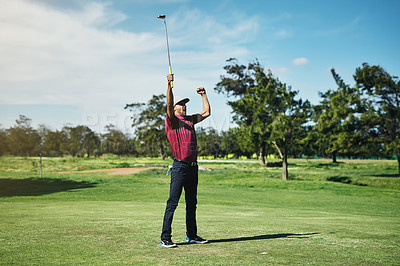 Buy stock photo Shot of a cheerful young male golfer lifting up his hands in success of playing a good shot outside during the day
