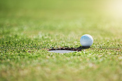 Buy stock photo Closeup shot of a golf ball on the edge of a hole outside on a golf course during the day