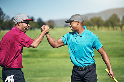 Buy stock photo Shot of two cheerful young male golfers engaging in a handshake after a great shot on the golf course