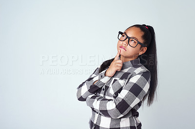 Buy stock photo Studio shot of a cute young girl looking thoughtful against a gray background