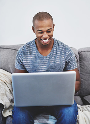 Buy stock photo Shot of a handsome young man using a laptop at home