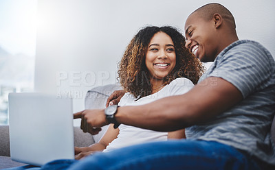 Buy stock photo Shot of a young couple using a laptop while relaxing at home