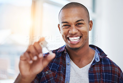Buy stock photo Cropped shot of a handsome young man holding house keys in his new home
