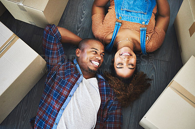 Buy stock photo High angle shot of an attractive young couple laying on the floor in their new home