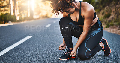 Buy stock photo Shot of a sporty young woman tying her shoelaces before her run