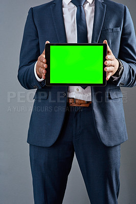 Buy stock photo Studio shot of an unrecognizable corporate businessman holding a tablet against a grey background