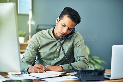 Buy stock photo Shot of a focused young businessman seated at his desk while taking on the phone and making notes inside the office