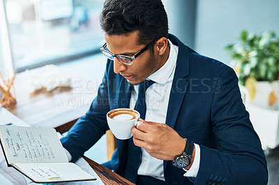 Buy stock photo Shot of a focused young businessman seated at his desk  while drinking coffee and reading his journal in the office
