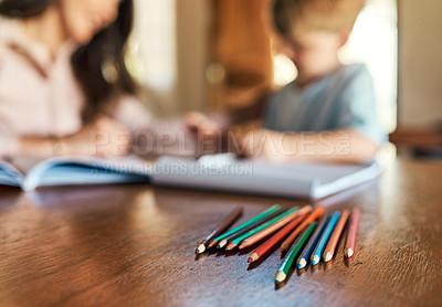 Buy stock photo Shot of pencils on a table with a mother and son doing homework in the background
