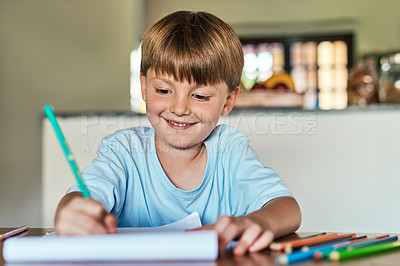 Buy stock photo Shot of a little boy sitting at a desk and writing on a notepad at home