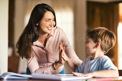 Buy stock photo Shot of a mother giving her son a high five while helping him with his homework