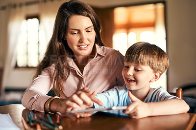 Buy stock photo Shot of a little boy using a digital tablet while doing homework with help from his mother