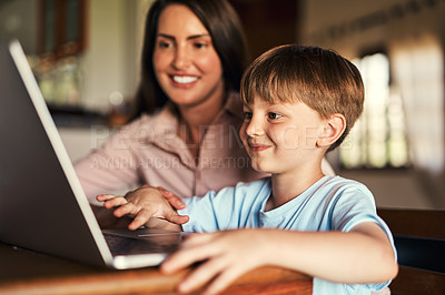 Buy stock photo Shot of an adorable little boy using a laptop with his mother at home