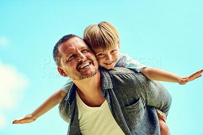 Buy stock photo Shot of a happy father and son enjoying a piggyback ride outdoors