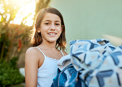 Buy stock photo Portrait of a little girl hanging up laundry outside