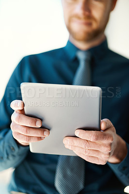 Buy stock photo Cropped shot of an unrecognizable businessman working on a digital tablet