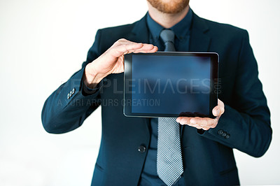 Buy stock photo Cropped shot of an unrecognizable businessman holding up a digital tablet