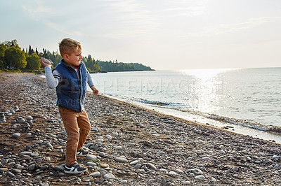 Buy stock photo Full length shot of an adorable young boy playing outside near a lake