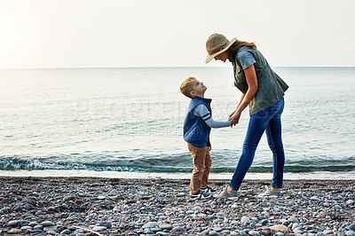 Buy stock photo Shot of a young woman and her son enjoying a walk by the water