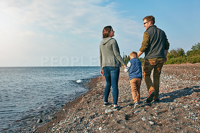 Buy stock photo Rearview shot of a young family walking by the lake