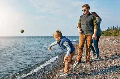 Buy stock photo Shot of a little boy throwing a rock into the lake while his parents watch him