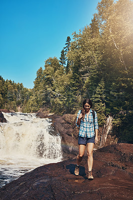 Buy stock photo Shot of an attractive young woman standing next to a rocky river and waterfall