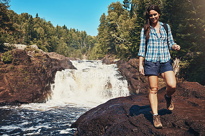 Buy stock photo Shot of an attractive young woman walking next to a rocky river and waterfall