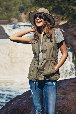 Buy stock photo Shot of an attractive young woman standing next to a rocky river