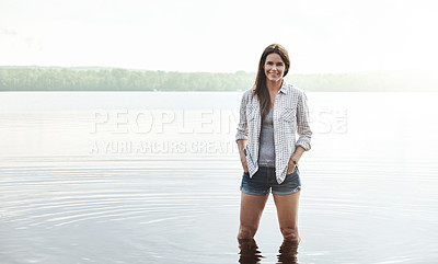 Buy stock photo Portrait of an attractive young woman standing in a lake