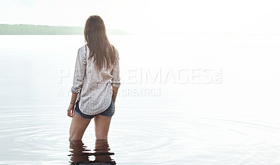 Buy stock photo Rearview shot of a young woman standing in a lake
