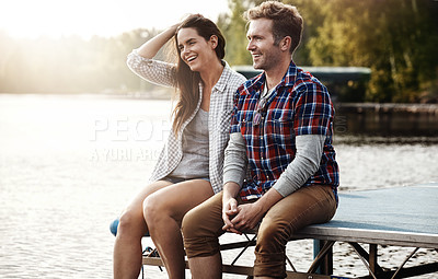 Buy stock photo Shot of a happy young couple sitting on a pier