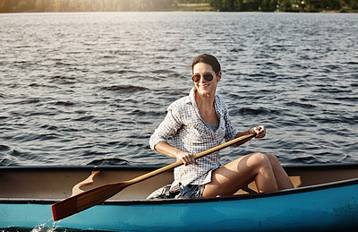 Buy stock photo Shot of an attractive young woman out for canoe ride on the lake