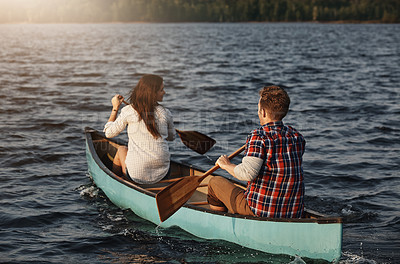 Buy stock photo Rearview shot of an unrecognizable couple rowing a boat out on the lake