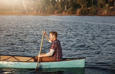 Buy stock photo Shot of a young man rowing a boat out on the lake