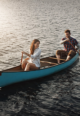 Buy stock photo Shot of a young couple rowing a boat out on the lake