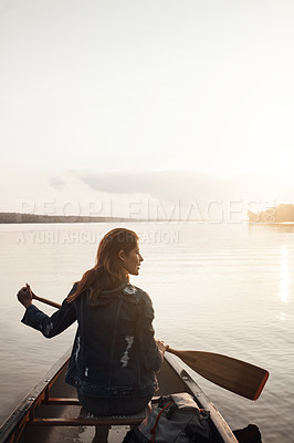 Buy stock photo Rearview shot of a young woman enjoying a canoe ride at the lake
