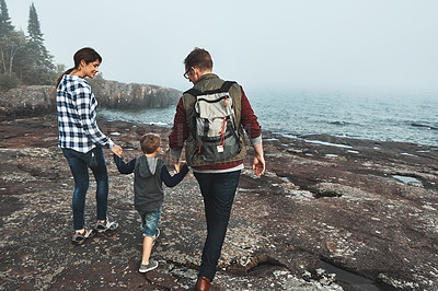 Buy stock photo Rearview shot of a cheerful young family holding hands and walking together next to the ocean outside during the day