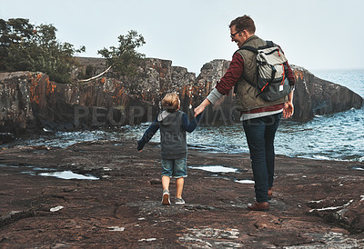 Buy stock photo Rearview shot of a cheerful father and son holding hands while walking next to the ocean outside during the day