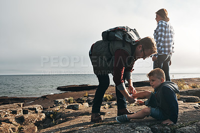 Buy stock photo Shot of a cheerful man helping to put his son's shoes on while standing next to the ocean outside during the day