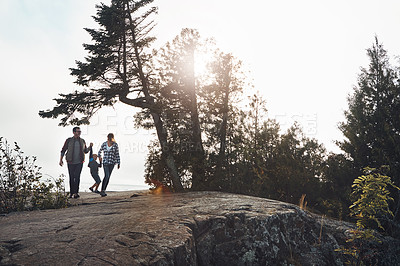 Buy stock photo Wide shot of a cheerful young family holding hands and walking together down a hill outside during the day