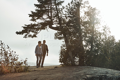 Buy stock photo Shot of a young couple out for a walk in nature