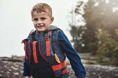 Buy stock photo Portrait of a cheerful little boy wearing a lifejacket while looking at the camera outside during the day