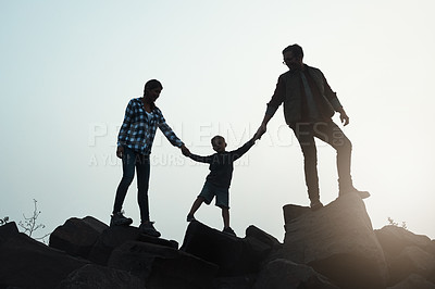 Buy stock photo Wide shot of a silhouette of a young family holding hands while walking on rocks with the sun peeking out in the horizon