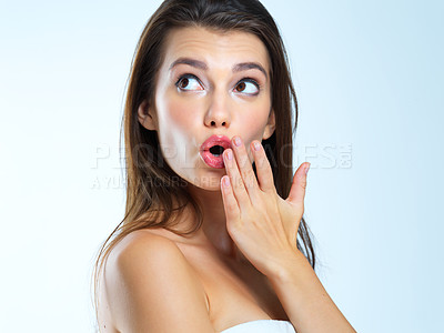 Buy stock photo Studio shot of a beautiful young woman looking surprised against a blue background