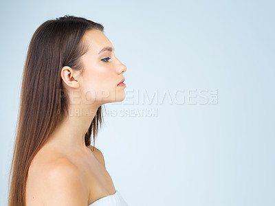 Buy stock photo Studio shot of a beautiful young woman posing against a blue background