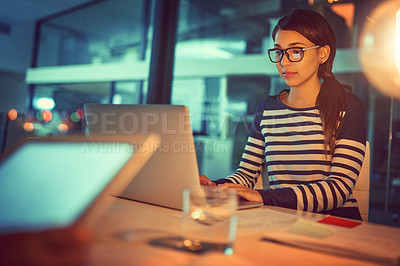 Buy stock photo Shot of a young designer working late in a laptop in an office